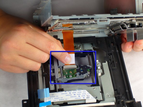 Image 3/3: Carefully remove the orange ribbon cable from the laser by gently pulling on the white plastic strip.