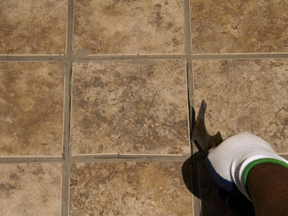 Use the painter's tool or putty knife to pry up the broken tile.