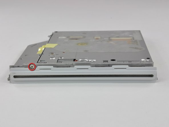 Remove the single Phillips screw securing the bezel at the front of the optical drive.