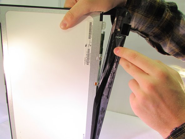 Pull the black tape that is attached to the frame off of the screen