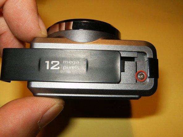 Retirez la vis du côté droit, sous le capot latéral. Le couvercle latéral est fixé à la caméra par l'une des vis en bas, et le couvercle doit facilement glisser vers le bas pour révéler la vis.