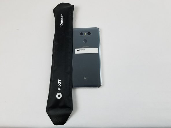 Apply the heated iOpener to the  edge of the phone for about 2 minutes.