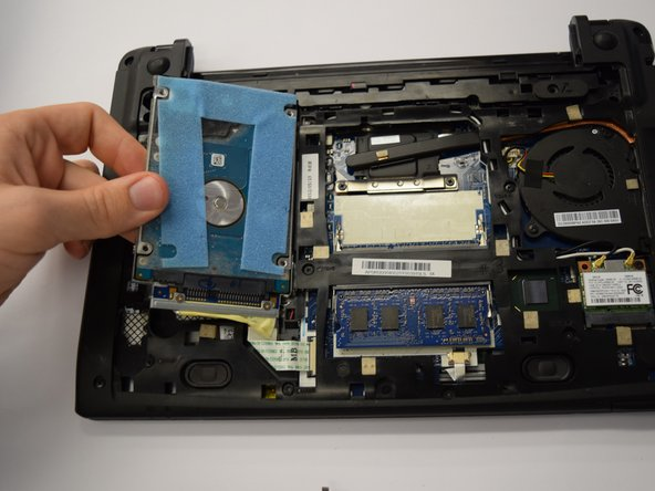 Image 2/2: While holding down the tabs, slide the ribbon cable to the left to remove it from the laptop.