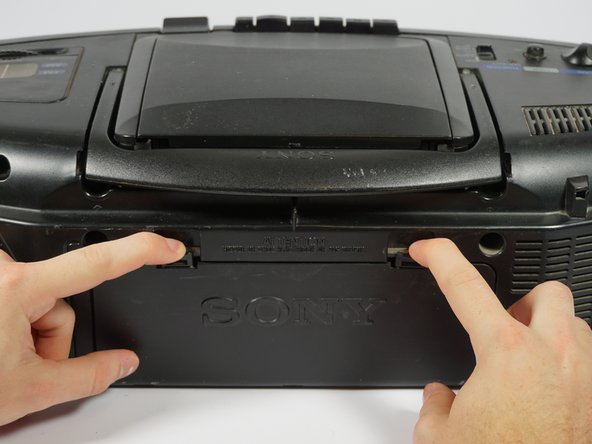 Remove the battery cover on the back of the boombox by applying downward pressure to the two clamps.