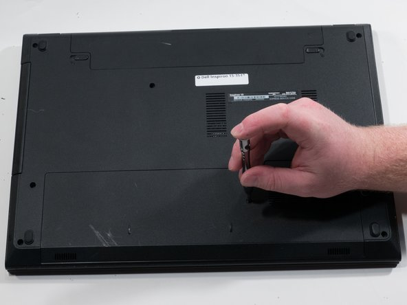Using a #0 Phillips screwdriver, remove the 2.0mm screw from the back of the device beside the vents.