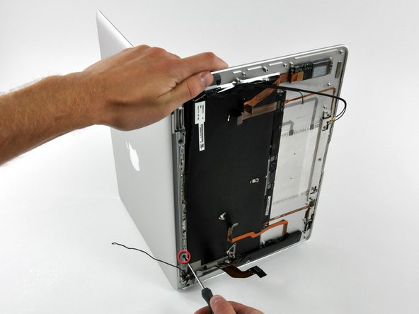 Image 1/1: While holding the top of the Air with one hand, remove the T6 Torx screw from the lower display bracket.