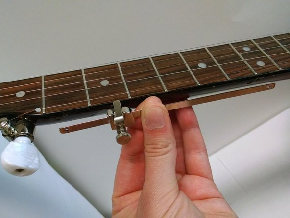 Image 1/3: Line the capo screw holes up about 12 mm from the fifth fret bar and about 4 mm from the face of the fret.