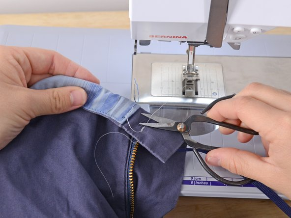 Lift the presser foot and remove the garment from the sewing machine.
