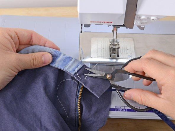 Den Nähfuß anheben und das Kleidungsstück aus der Nähmaschine nehmen.