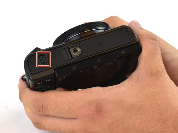 On the bottom of the camera, slide the latch on the battery cover toward the center of the camera.