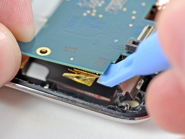 Use the edge of an iPod opening tool to pry the rear-facing camera connector away from its socket on the logic board.