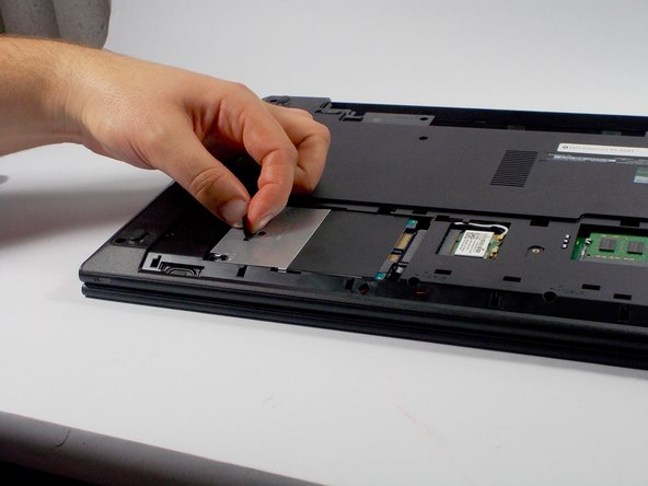 Carefully pull on the tab on the hard drive to slide it out away from the connector.