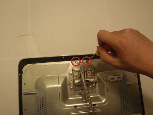 Remove the two phillips head screws near the cable attachment with the phillips head screwdriver.