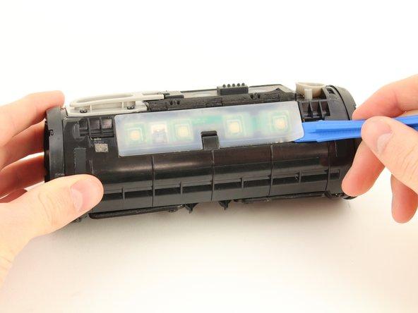 Führe das Öffnungswerkzeug unter die durchsichtige Gummiabdeckung über der Tastensteuerplatine ein.