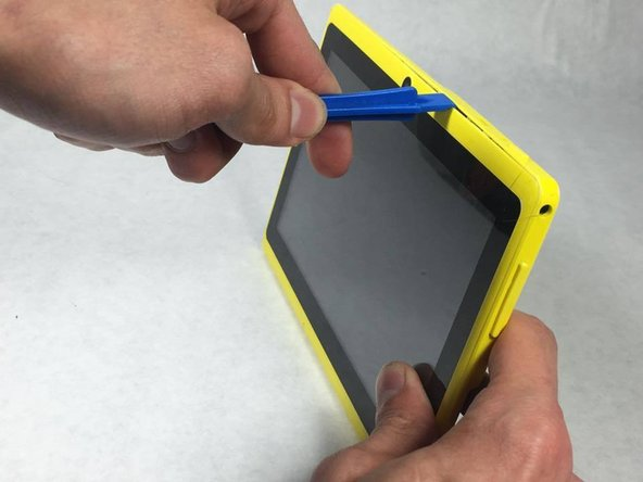 Begin by popping off the plastic yellow device casing with the soft tip prying tool.