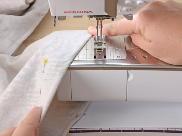 Thread the sewing machine, using a thread color that matches your garment's fabric as closely as possible.