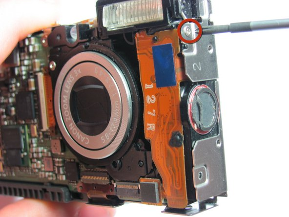 Remove the 3.4 mm  Phillips screw on the right side of the camera