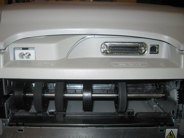 Remove the paper jam door from the printer by turning the dial from the locked position to the unlocked position.