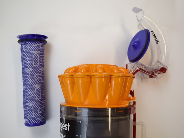 Lift up the clear handle to reveal the main cylindrical filter. Pull out the purple filter piece to replace.