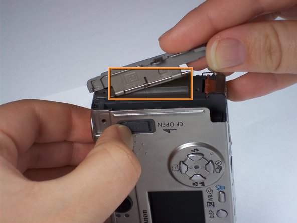 Remove the memory card cover by sliding down the CF open button and moving the pin.