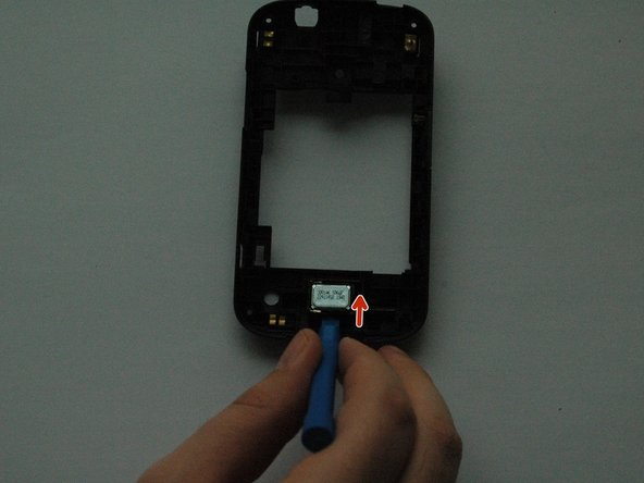 Using the plastic opening tool, gently lift the speaker out of the back case.