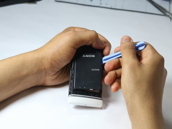 Image 1/1: Use the plastic opening tool to pry up on the side of the battery, then remove the battery and set it aside.