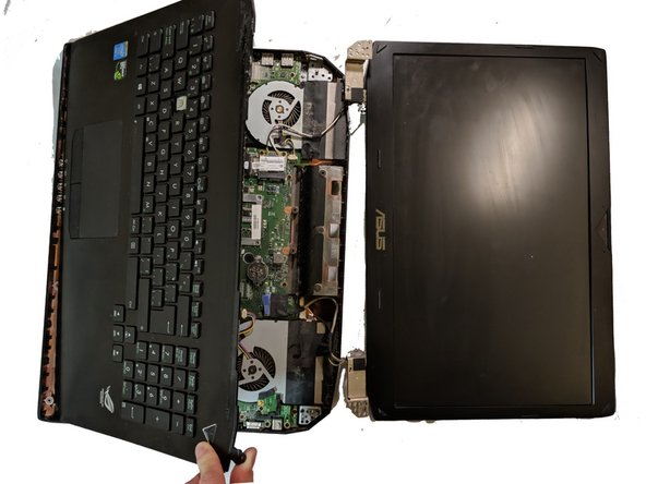 Use a metal separator to carefully separate the bottom half of the laptop.