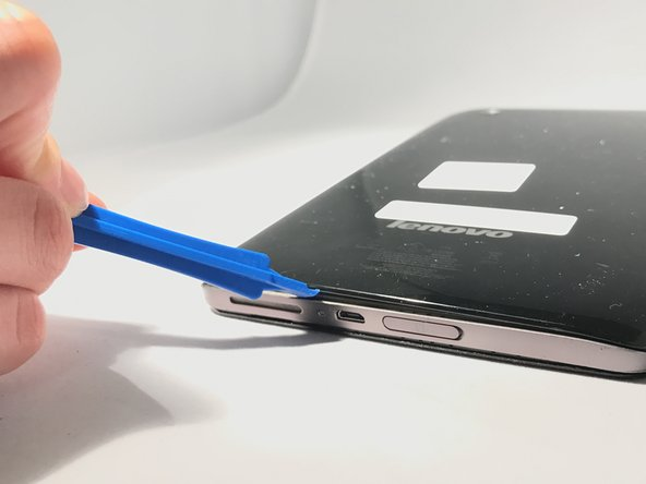 Insert a plastic opener in-between the black back panel and the silver body of the tablet.