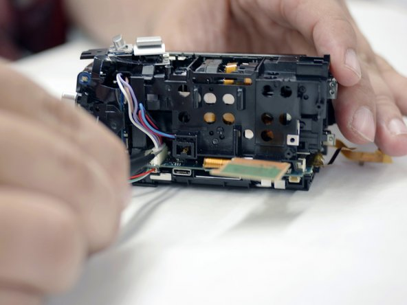 Orienting the camera such that the right side is facing you, remove the wire harness connecting the lens assembly to the motherboard using your tweezers.