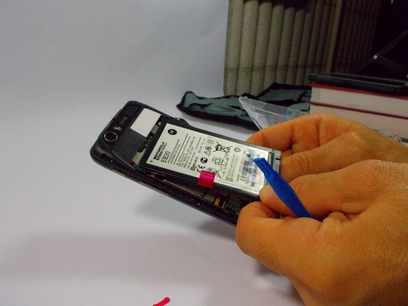 Image 3/3: Once the battery is loose, carefully lift from the bottom edge and remove the battery.