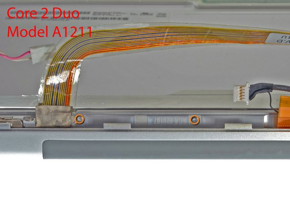 Image 2/2: If you have a Core 2 Duo Model A1211 machine, refer to picture 2 and remove two Phillips screws connecting the clutch assembly to the lower edge of the front display bezel near the display data cable.