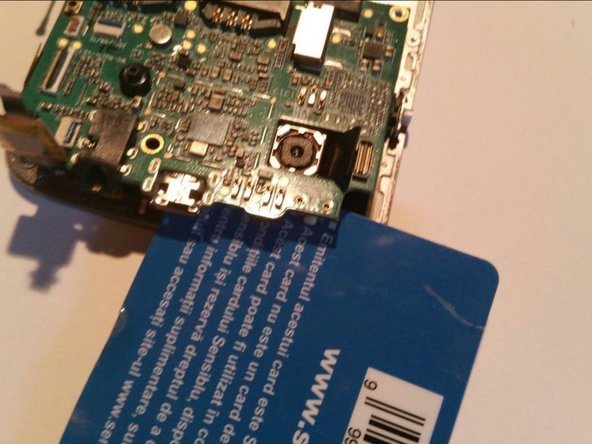 After all cables have been released we can remove the logic board, by gently prying it up with our card.