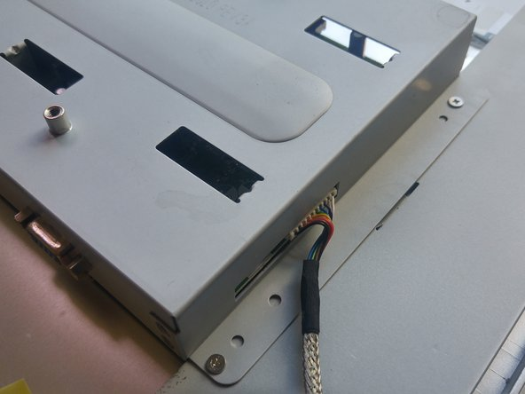 There are four screws on each side of the monitor that you must remove to disassemble the rest of the monitor