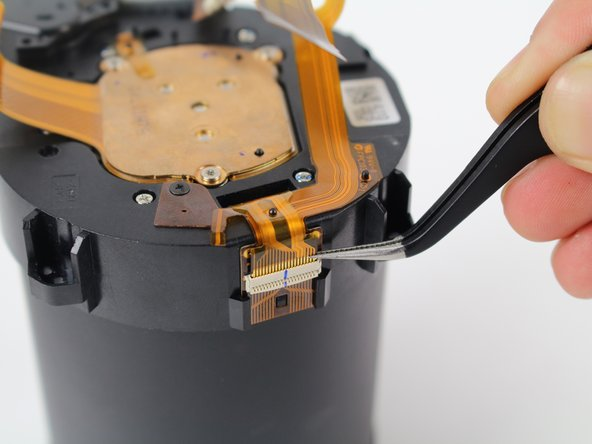 Using tweezers, very carefully pull to disconnect the ZIF connector ribbon between the lens and the metal cylinder.