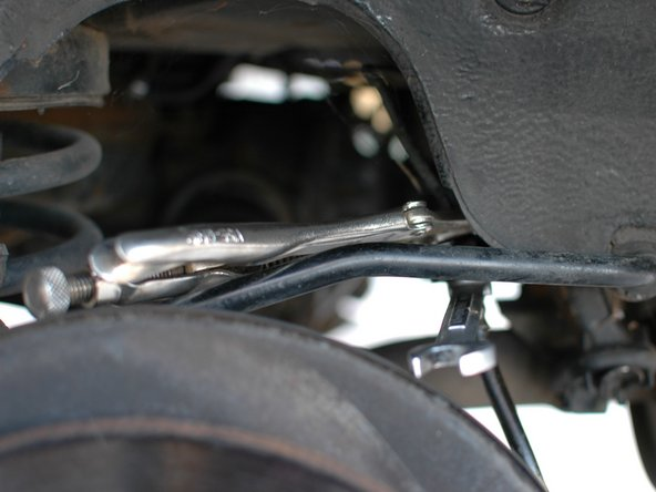 In the occasion that the upper connection of the hose, where it connects to the hard line, is corroded to the extent where the 11mm nut rounds off while attempting to remove the line you may need to clamp the 11mm rounded off nut in a pair of locking pliers in order to get enough of a hold on it to break the lower 14mm nut on the soft line free.