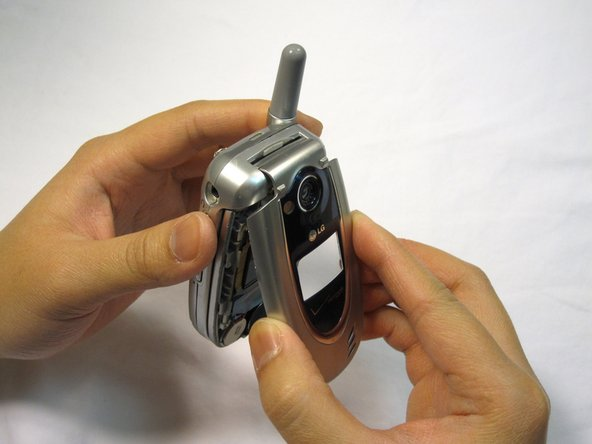 Image 1/3: Hold the base of the phone and gently remove the faceplate.