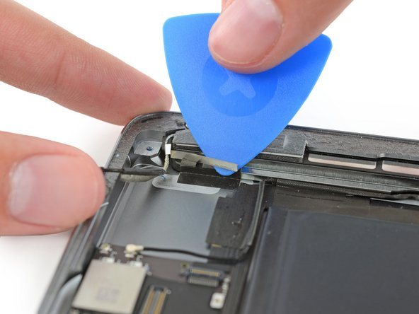 Slide the pick toward the home button to cut the adhesive.