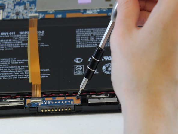 Gently remove the gold ribbon cable covering the battery and set it aside.
