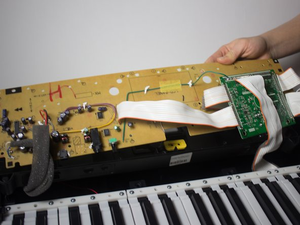 Once all the screws have been removed, lift the component board and place it face down on the keys.