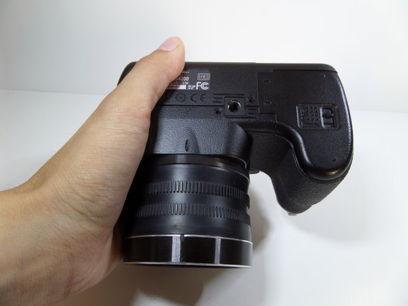 Image 1/1: Begin with the camera upside down so that the battery compartment is showing.
