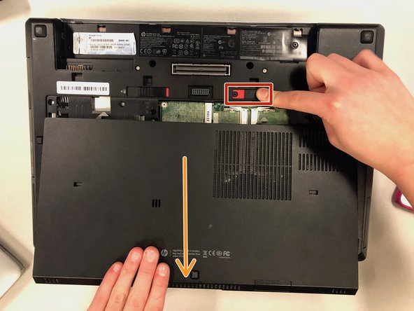 To begin, you will need to remove the battery by sliding the left slider (red) to the left.