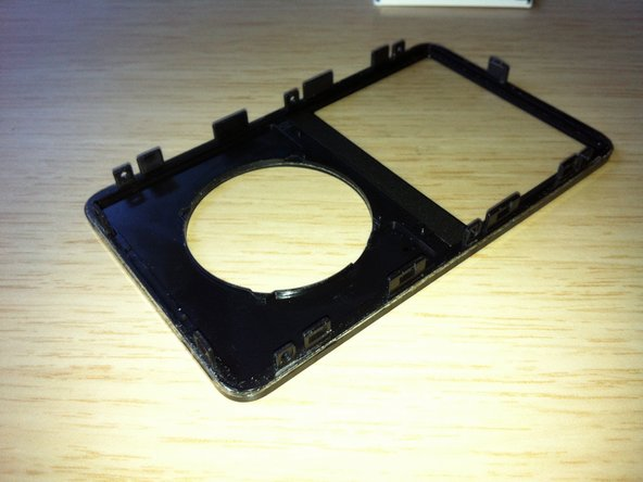 Image 1/1: Use this photo of the OPENED iPod for the reference, in order to locate the areas where the retaining clips are - 4 per side, one on top and two at the bottom. It should save you a lot of frustration and help avoid scratching the plastic cover.