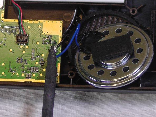 Image 2/2: After you have finished this step and the wire ends have cooled, you can safely set the removed speaker aside.
