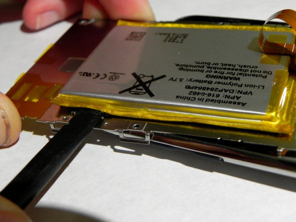 Rotate the metal display tray to the top of the iPod, being careful of the ribbon connecting the battery to the logic board.