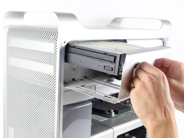 Firmly grasp the handles of the shown compartment and pull out firmly to remove the optical drive bay.
