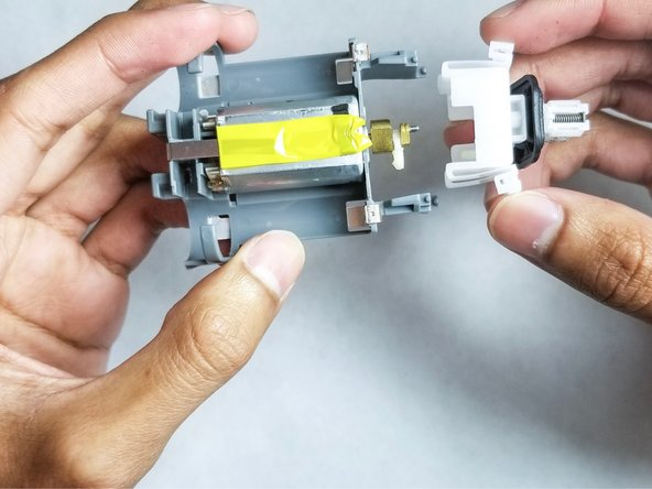Detach the white plastic blade base from the tip of the motor by  pulling it.