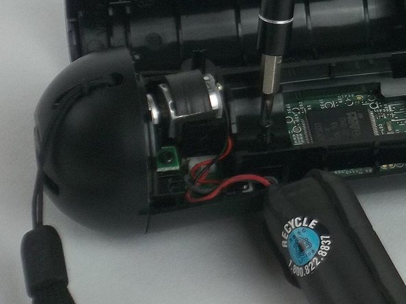 Using a Phillips head screwdriver, remove the 9mm screw located to the right of the battery, which is connected to  the inner plastic frame.