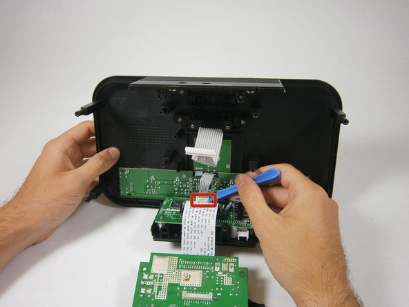 Use a plastic opening tool to pry and lift up the white zip connector holding the LCD screen to the buttons.